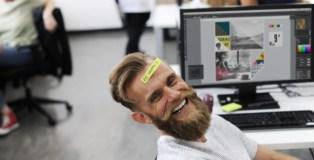man smiling in chair at office desk