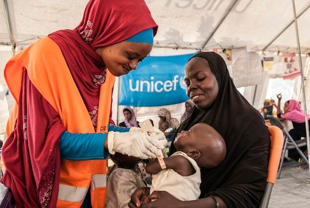 A UNICEF official assessing a seven-month old baby. Credit:UNICEF