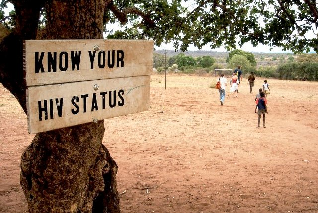 "Placard hangs on a tree with inscription: ""know your HIV status""."