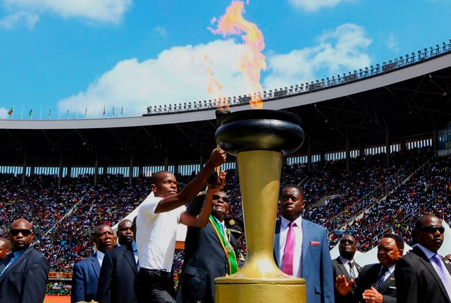 Zimbabwean President Robert Mugabe is assisted to light the anniversary flae
