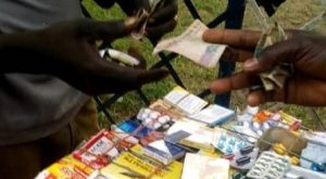 Drug peddler exchanging drug with money in Ijora, Lagos