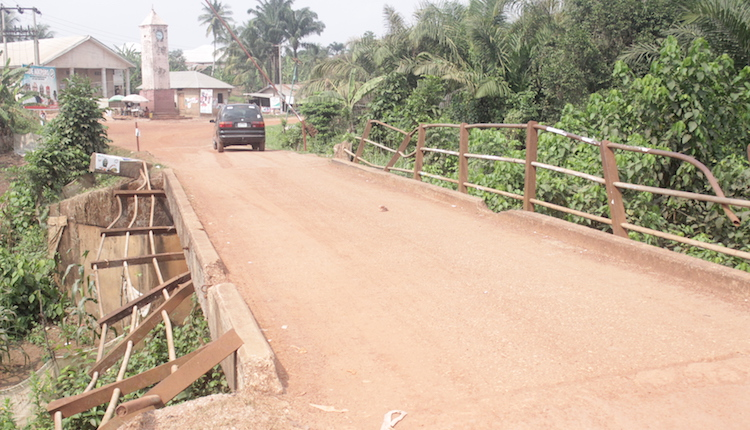 A bridge in the community has almost failed with bent hand rails as cars slowly navigate to avoid falling off. Photo by Patrick Egwu.JPG