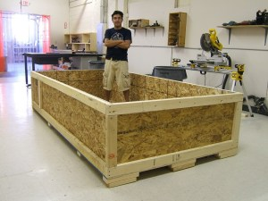 Large wooden Shipping Crate with Tony standing inside of it