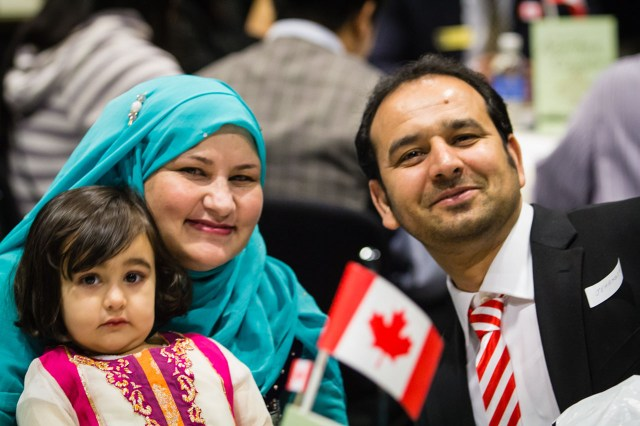 family smiling, child is holding canadian flag souvenir
