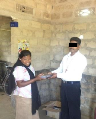 A woman happily accepts a Bible given to her by a pastor in Sri Lanka.