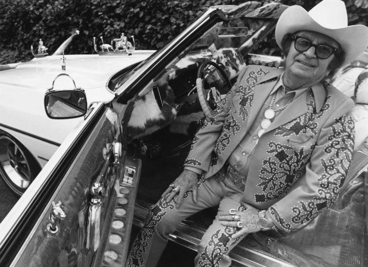 El diseñador de moda western Nudie Cohen sentado en su Pontiac descapotabe en 1971 | Marti Coale:BIPs:Getty Images