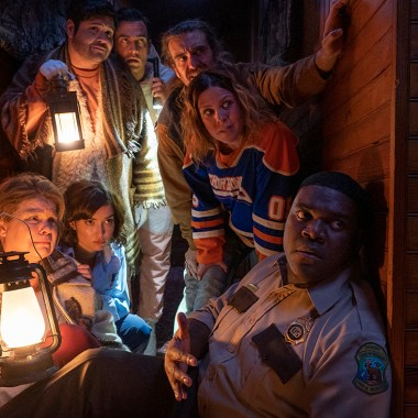 "(Left to right) Catherine Curtin as ""Jeanine Sherman,"" Milana Vayntrub as ""Cecily Moore,"" Harvey Guillen as ""Joachim Wolfson,"" Cheyenne Jackson as ""Devon Wolfson,"" George Basil as ""Marcus,"" Sarah Burns as ""Gwen,"" and Sam Richardson as ""Finn Wheeler"". Courtesy of Sabrina Lantos. An IFC Films Release."