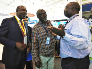 Dr Moses Siambi, Research Program Director - Eastern & Southern Africa and Country Representative, Kenya (far right) explains ICRISAT's work to Mr Willy Bett (far left) who visited the stall. Photo: K Rajani, ICRISAT