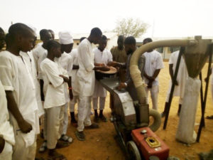 Students of the Government Secondary School, Rano, watch the operation of the hammer mill. Photo: ICRISAT