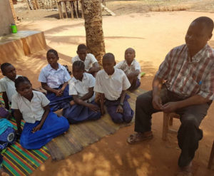 Students of Mnanje Primary School listen to Mr Agili Mrekoni talk about the Groundnut School Garden Program. Photo: C Ojiewo