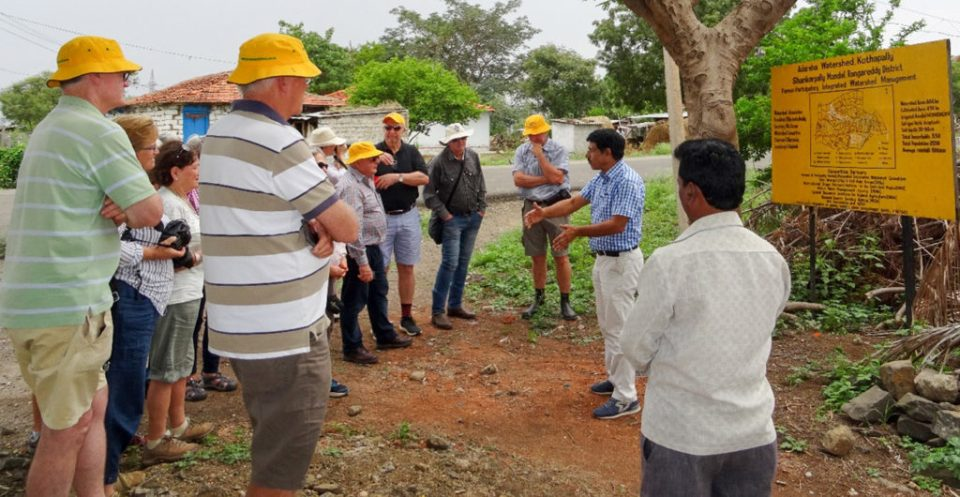 The visitors are all ears as they learn about low-cost soil and rainwater conservation and groundwater recharge systems.  Photo: DS Prasad Rao, ICRISAT