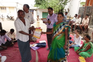 Farmer recieving his Soil Health Card from the Village President Kalamma. Photo: ICRISAT