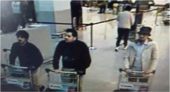 Two suspects were wearing identical dark clothes and gloved left hands, while the third, to their left, dressed in lighter clothing and a hat is suspected of fleeing the airport