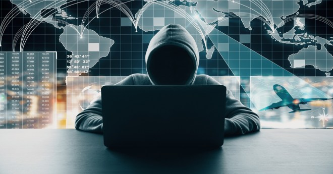 Dark Web danger represented by a hacker in a hoodie hunched over a black computer in front of a glowing world map representing records on the dark web