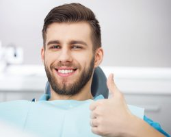 Portrait Of Happy Patient In Dental Chair.
