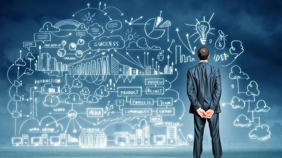Homem observando um quadro com rascunhos de ideias e etapas para alcançar o sucesso.