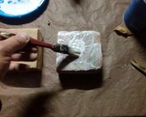 stendere colla vinilica sulla pietra per applicare immagini di carta