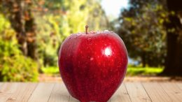 Red apple sitting on wooden picnic table