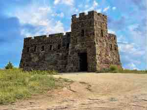 A picture of a small castle called Coronado Heights with a bright blue sky behind it