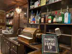 Picture of a prohibition era speakeasy with cash register and alcohol bottles lining the wall