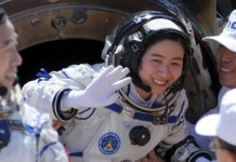 Liu Yang (C), China's first female astronaut, waves next to her comrade Jing Haipeng (L) as she comes out from the re-entry capsule of China's Shenzhou 9 spacecraft in Siziwang Banner, Inner Mongolia Autonomous Region June 29, 2012. China's Shenzhou 9 spacecraft returned to Earth on Friday, ending a mission that put the country's first woman in space and completed a manned docking test critical to its goal of building a space station by 2020. The spacecraft's gumdrop-shaped return capsule descended to Earth by parachute and touched down shortly after 10 a.m. (0200 GMT) in China's northwestern Inner Mongolia region with its three-member crew, including female astronaut Liu Yang. REUTERS/China Daily (CHINA - Tags: MILITARY SCIENCE TECHNOLOGY TPX IMAGES OF THE DAY) CHINA OUT. NO COMMERCIAL OR EDITORIAL SALES IN CHINA - RTR34CKG