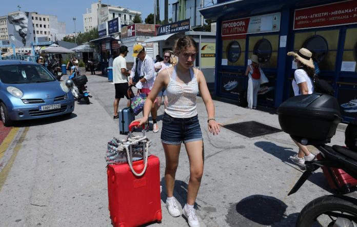 Τουρίστες ετοιμάζονται να επιβιβαστούν σε πλοίο της γραμμής στο λιμάνι του Πειραιά