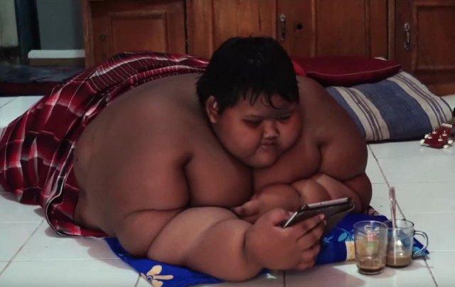 Ο Αρια ήταν το πιο χοντρό παιδί του κόσμου. Ξαπλωμένος παίζει με tablet.