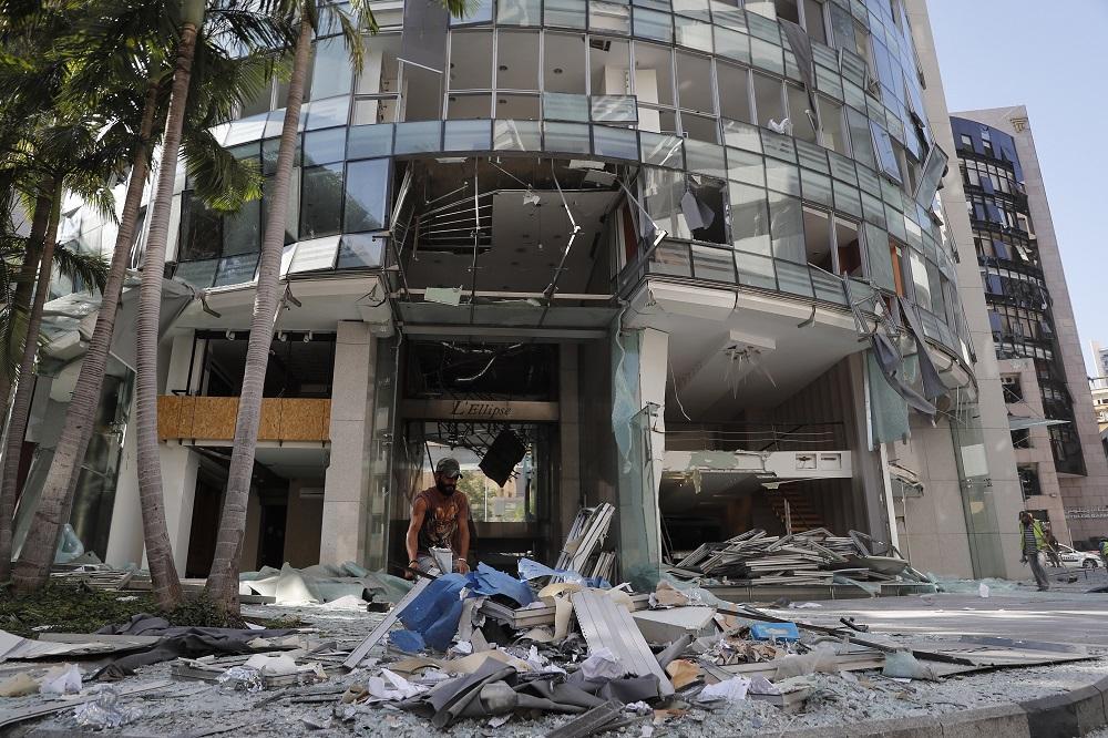 Ανδρας έξω από κατεστραμμένη πολυκατοικία