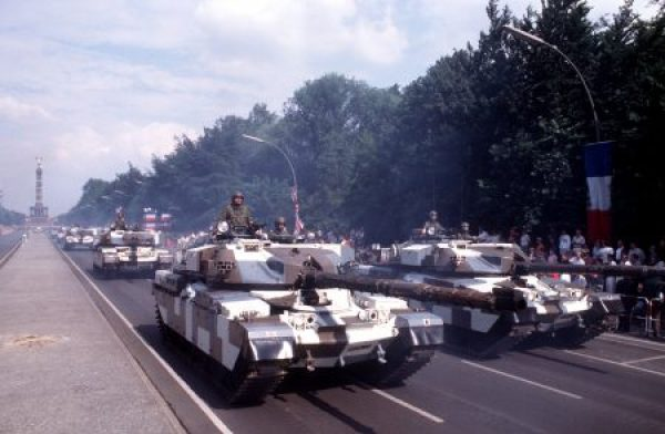 "Two columns of British Army Fox armored combat reconnaissance vehicles drive along 17th of June Street during the annual Allied Forces Day parade. The ""Siegessaulte"" (Victory Column) is in the background."