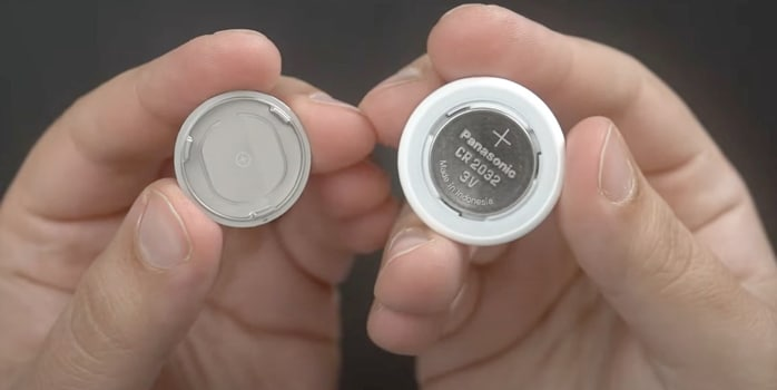 Осторожно нажмите на крышку батарейного отсека из нержавеющей стали AirTag.