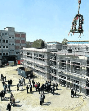 Der Kranz schwebt: An der IGS Kaufungen wurde gestern Richtfest gefeiert, links der PCB-belastete Altbau, der abgerissen wird. Foto: Herzog