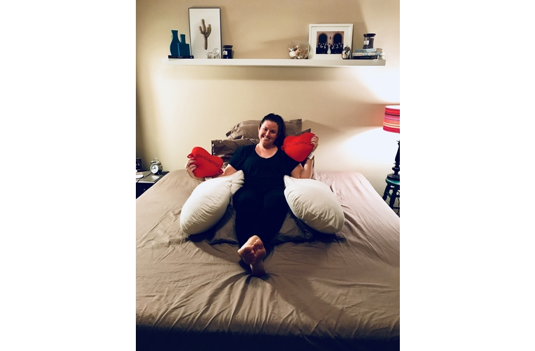 Mackenzie sitting on bed in mastectomy pillow fort with heart pillows
