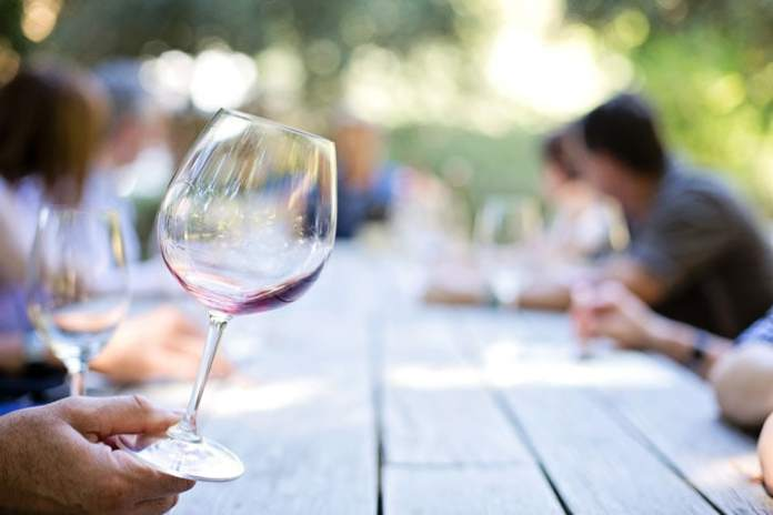 Wineglass and people talking around table