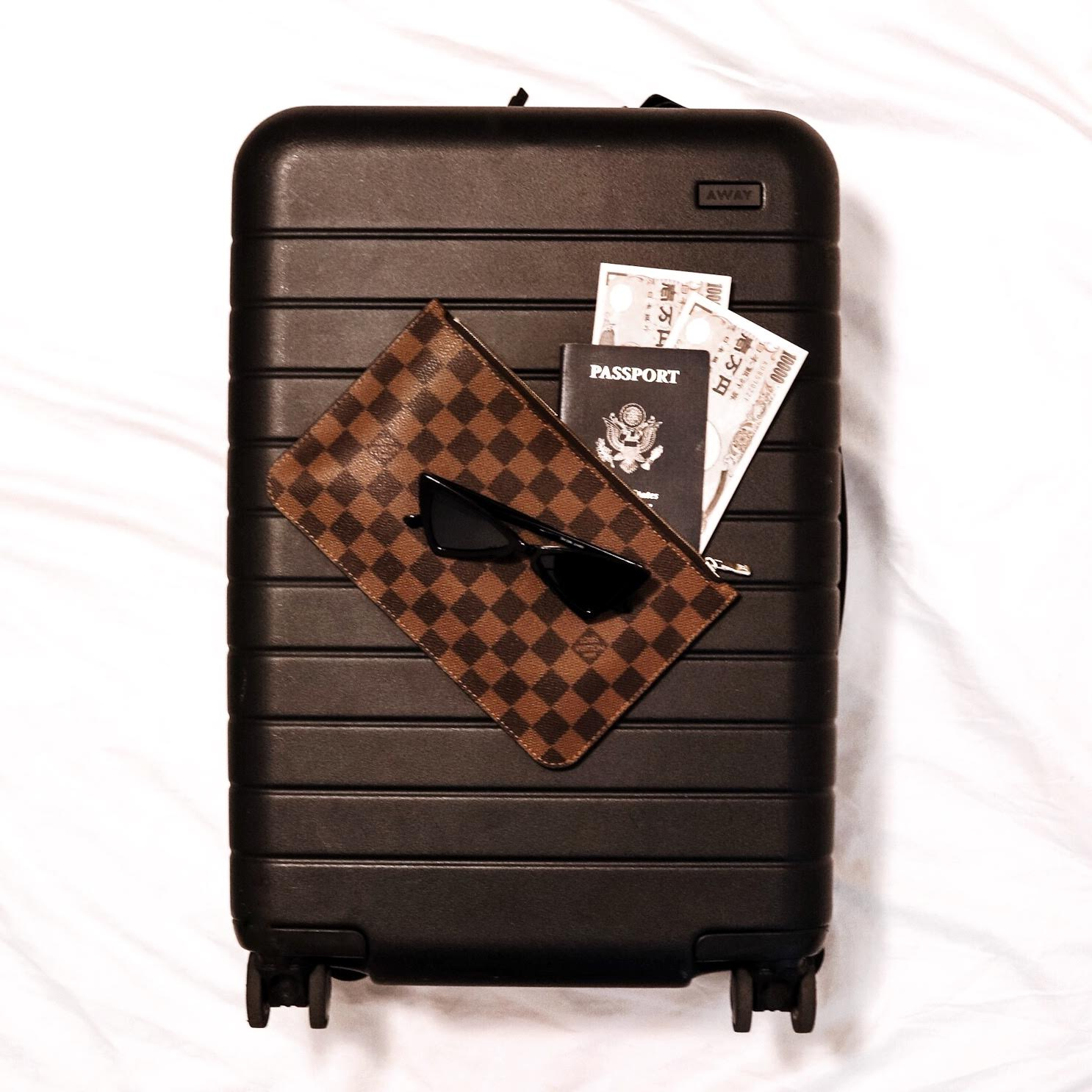 Away bigger carry on black, Louis Vuitton pouch, travel flatlay