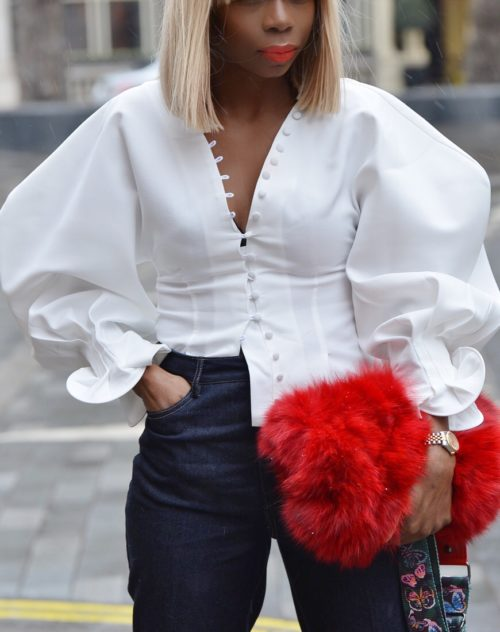 Black model in black owned spring fashion puffy sleeved shirt, with red fur back, black pants and blonde wig