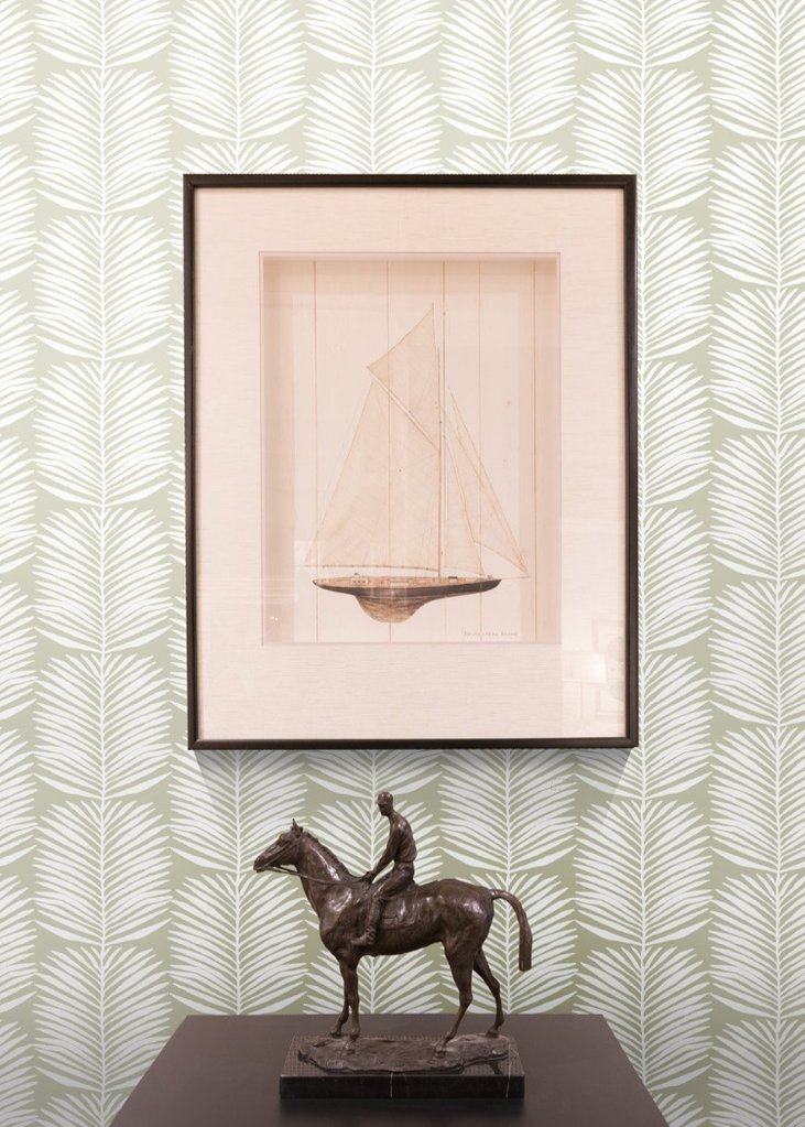 Sculpture of man riding horse on black table and boat wall art from black owned home decor brand