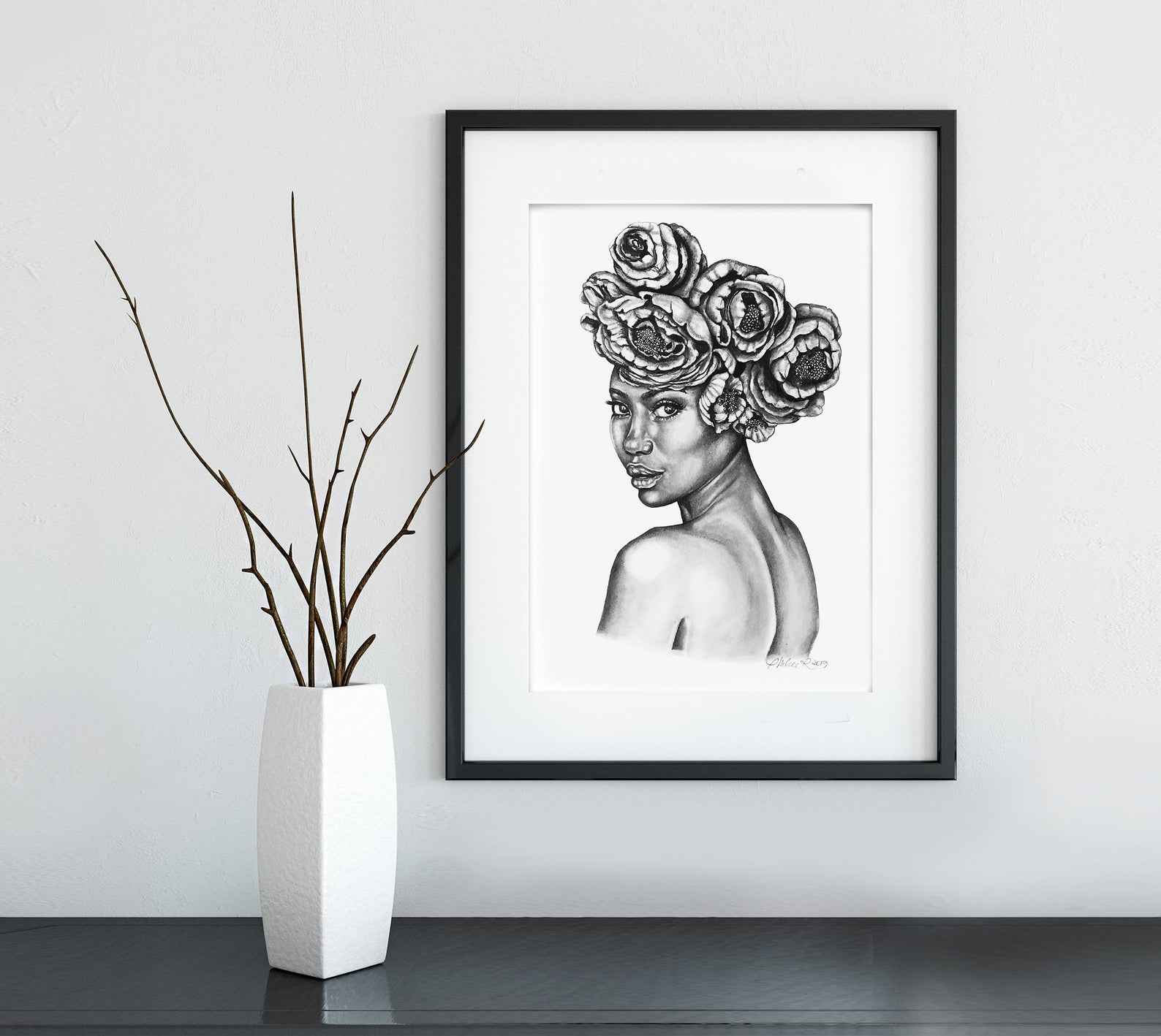 Branches in white pot and image in black frame on wall from black owned home decor brand