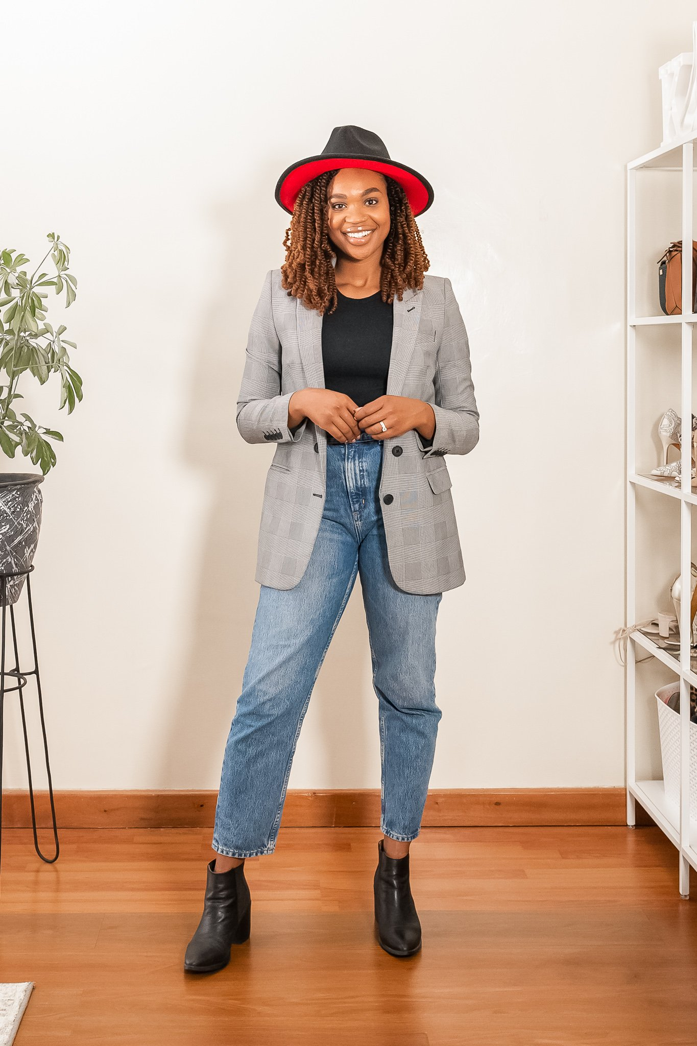 Ijeoma Kola showing how to style a fall blazer with black top, blue mom jeans, back ankle boots and black hat.