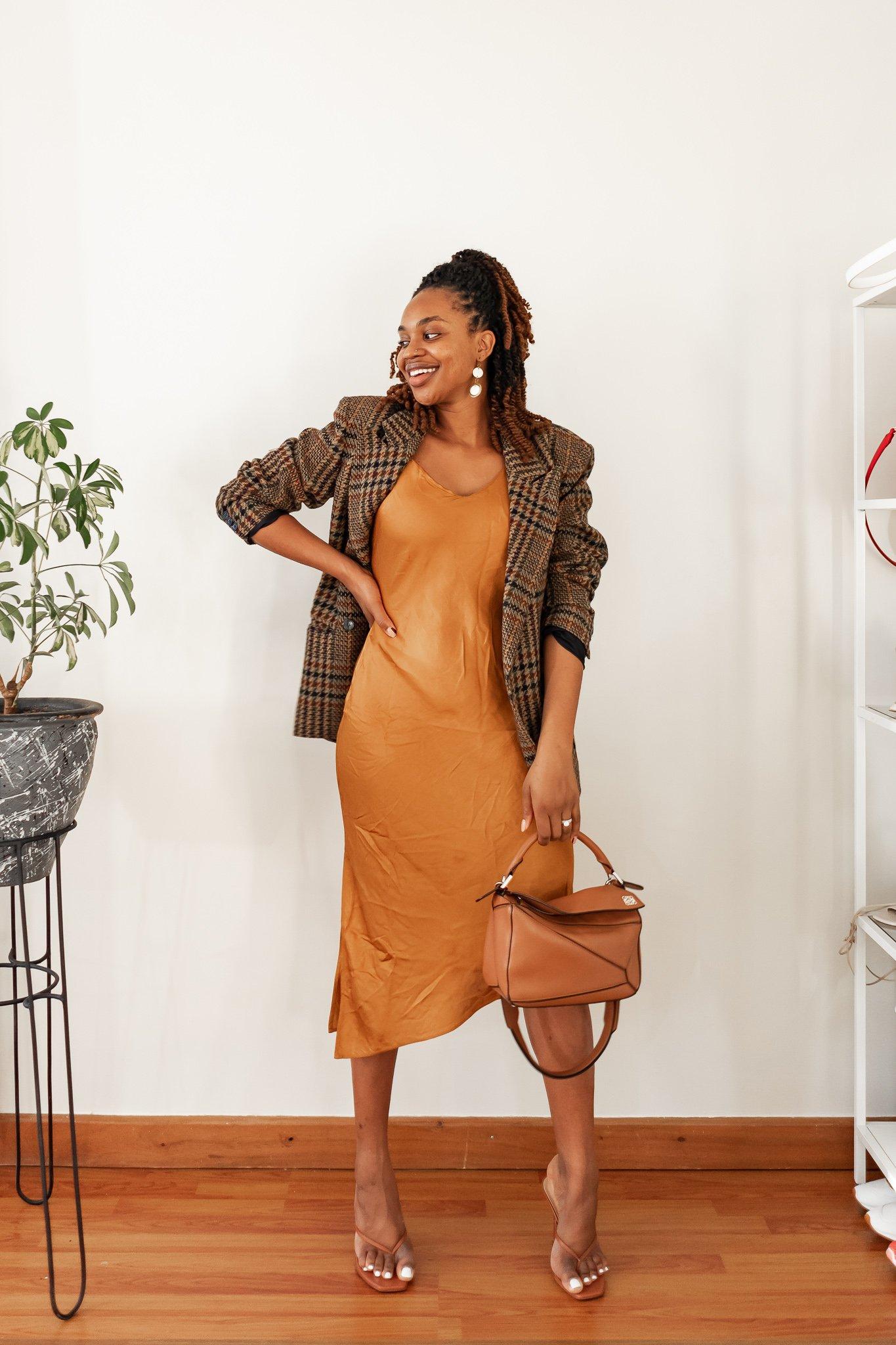 Ijeoma Kola in orange slip dress, tweed blazer, brown handbag, and heel sandals