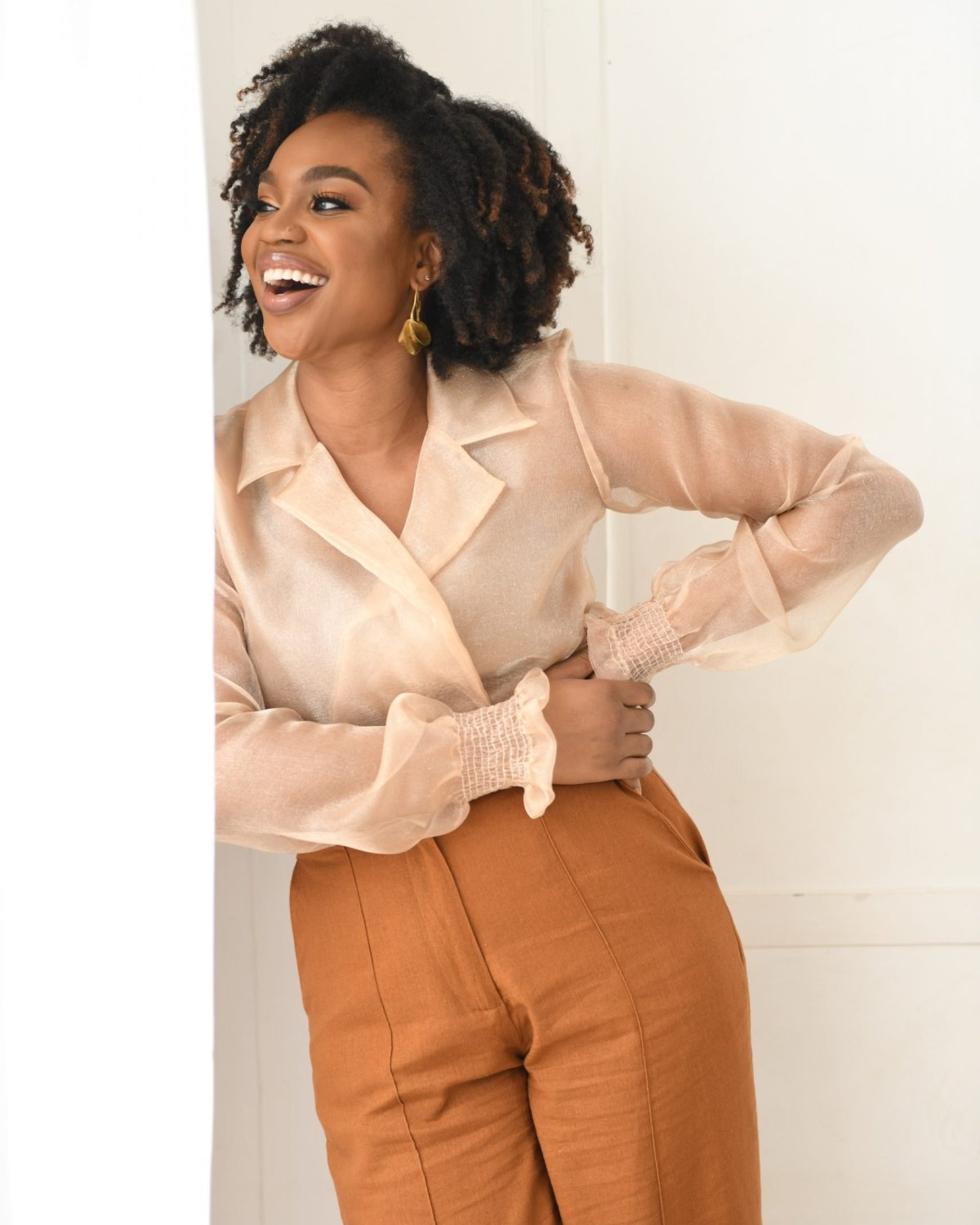 Ijeoma Kola in sheer top and orange pants