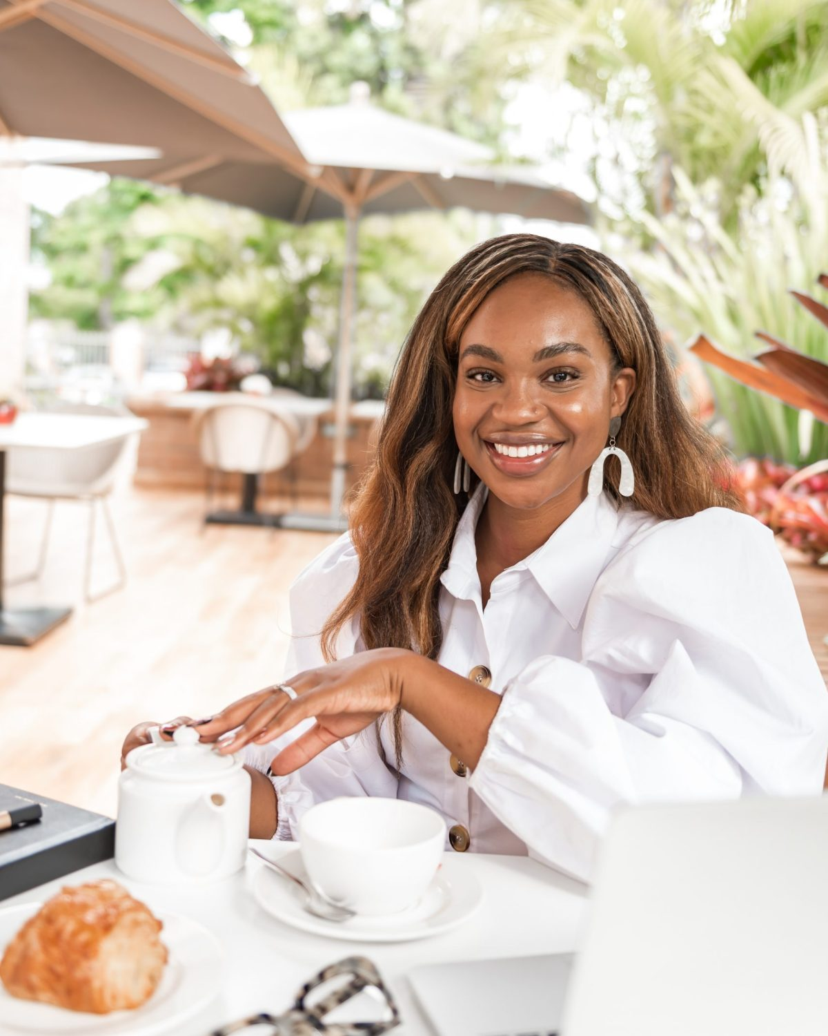 Ijeoma Kola sitting at café for tea, with laptop and glasses on table - Blog about social media and mental health
