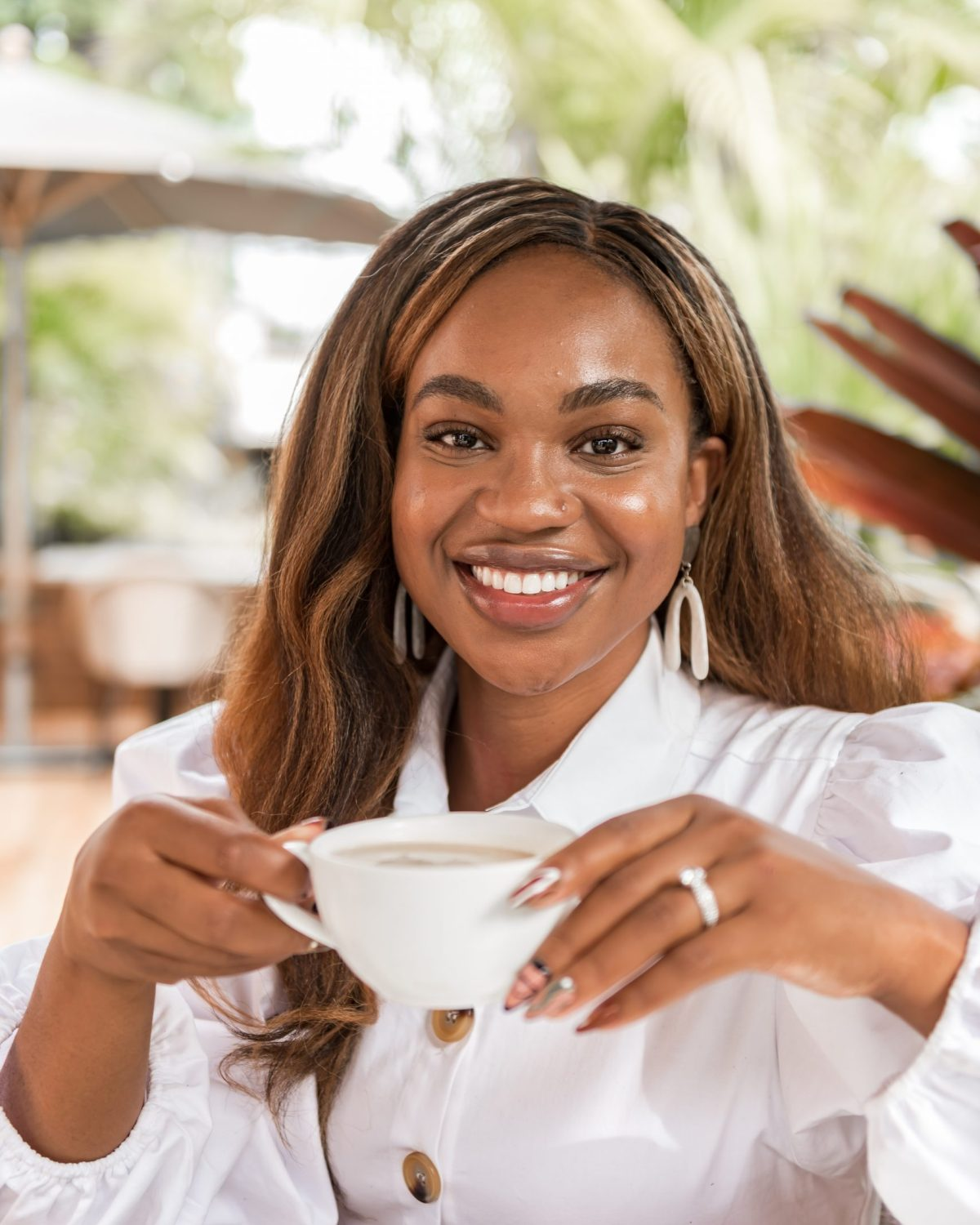 Ijeoma Kola smiling with tea cup in hands, wearing white shirt - Blog on social media and mental health
