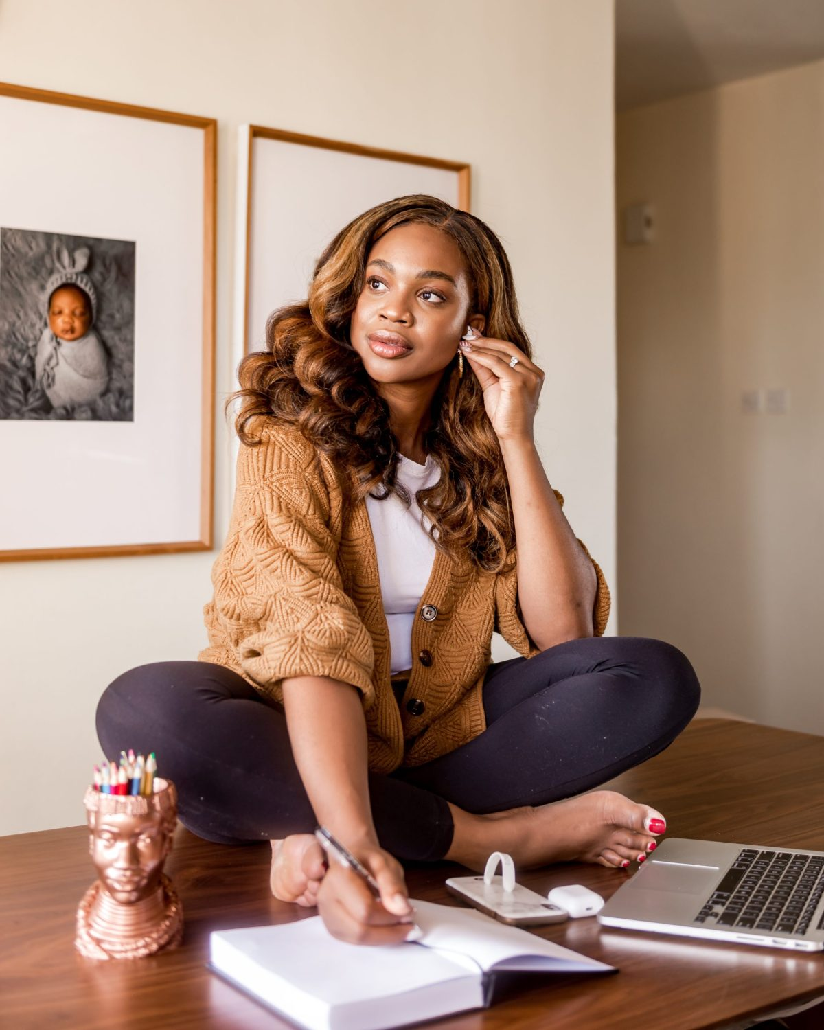 Ijeoma Kola sitting on table with laptop,looking into the distance. Framed photo of baby on the wall in the background - Working from home with a toddler