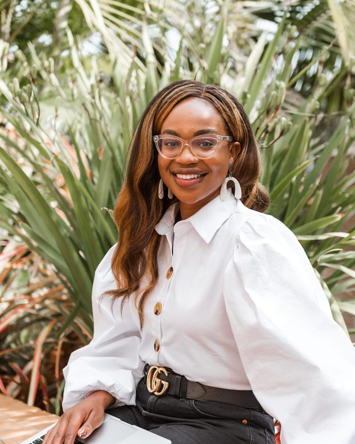 Ijeoma Kola sitting outdoors and smiling with computer on lap - Blog giving advice on changing careers