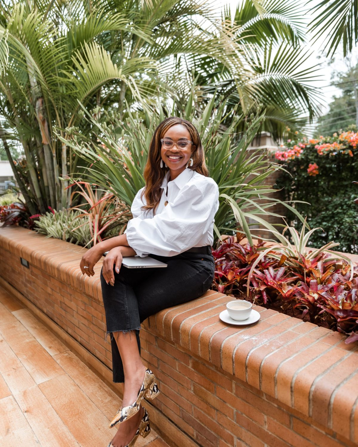 Ijeoma Kola sitting outdoors and smiling with laptop closed on lap and cup of tea next to her
