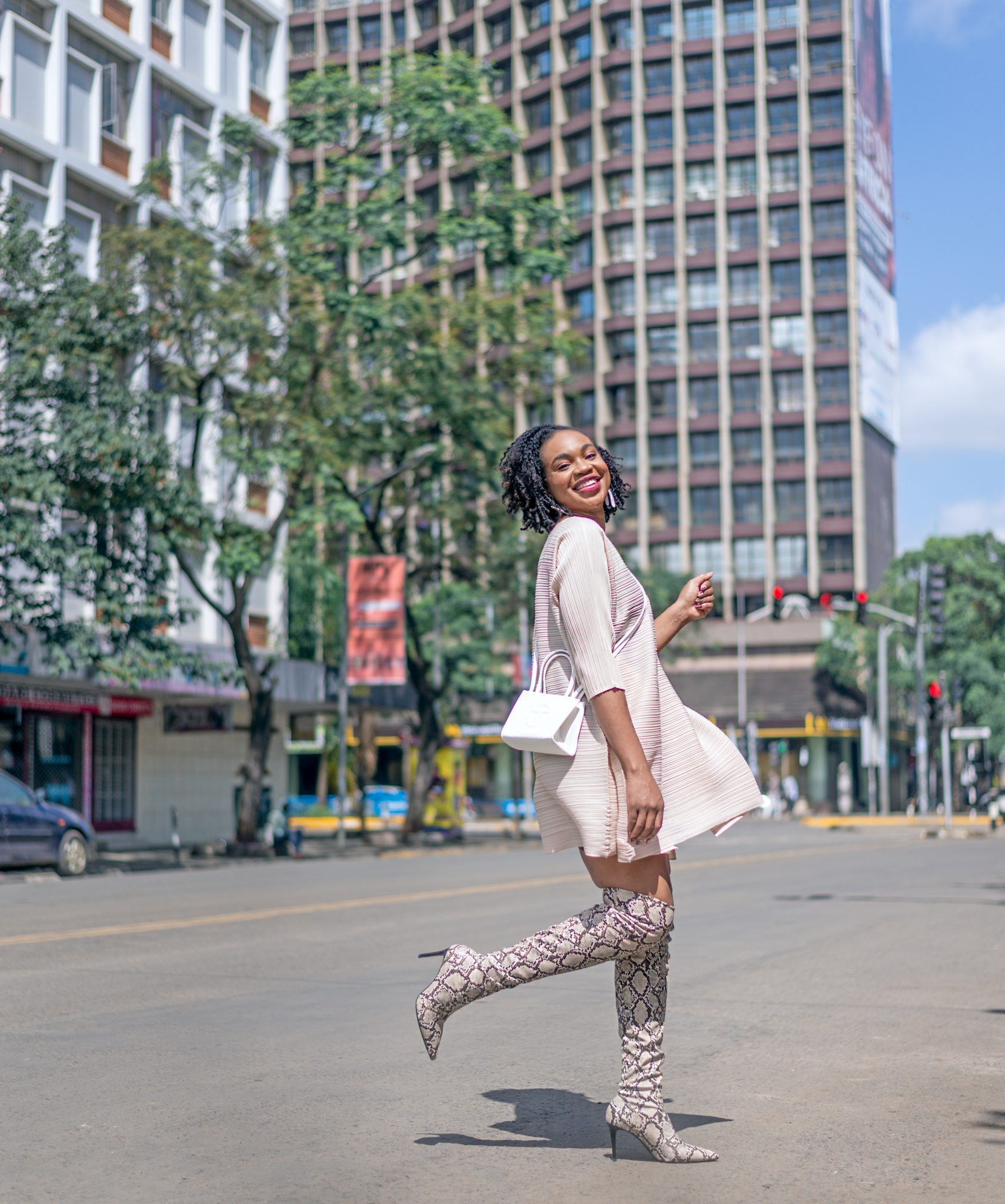 Ijeoma Kola kicking leg up while posing in the streets of Nairobi wearing cream mid-sleeve dress, white shoulder sling bag and snake skin thigh high boots