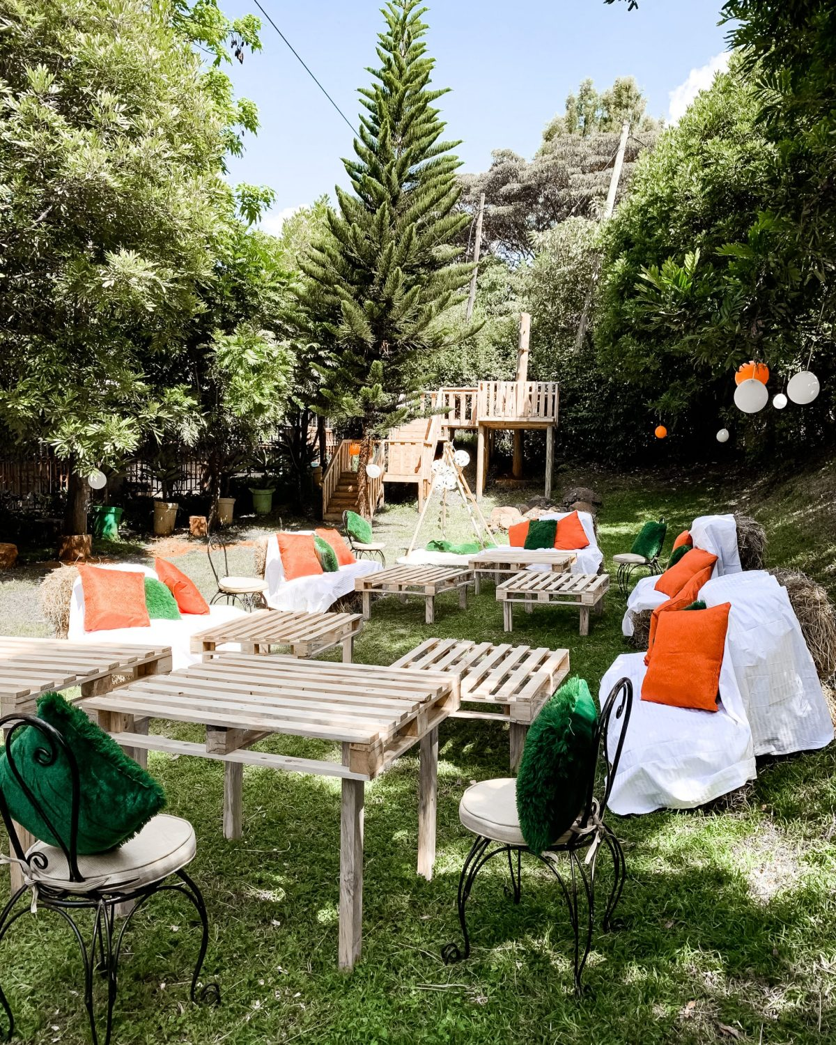 Picnic seit up with wooden pallet furniture and orange and green pillows - baby birhtday party ideas