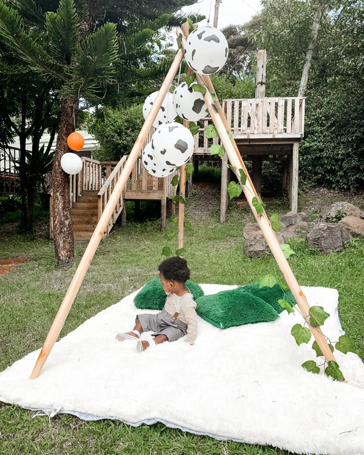 Black baby boy sitting on picnic mat underneath wooden teepee structure - baby birthday party ideas