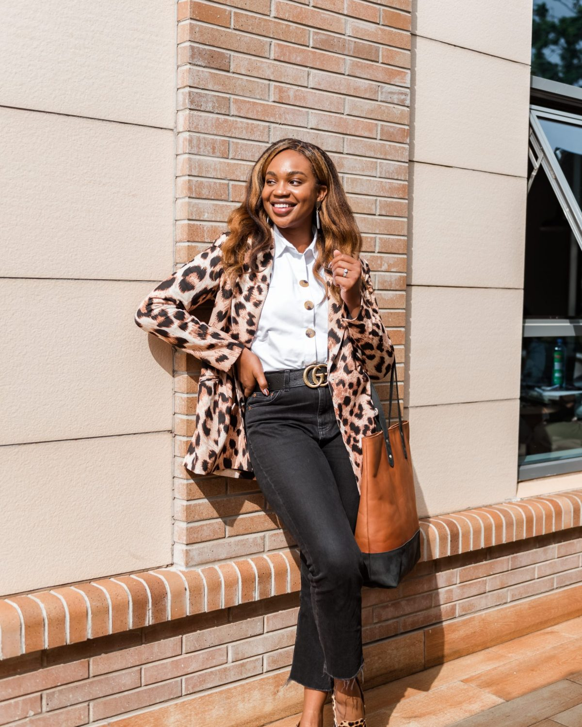 Full outfit shot of Ijeoma Kola posing outside with hand on hip wearing animal print blazer, white shirt, black pants and animal print shoes - How Black Owned Businesses Can Optimize Black History Month to Grow Business