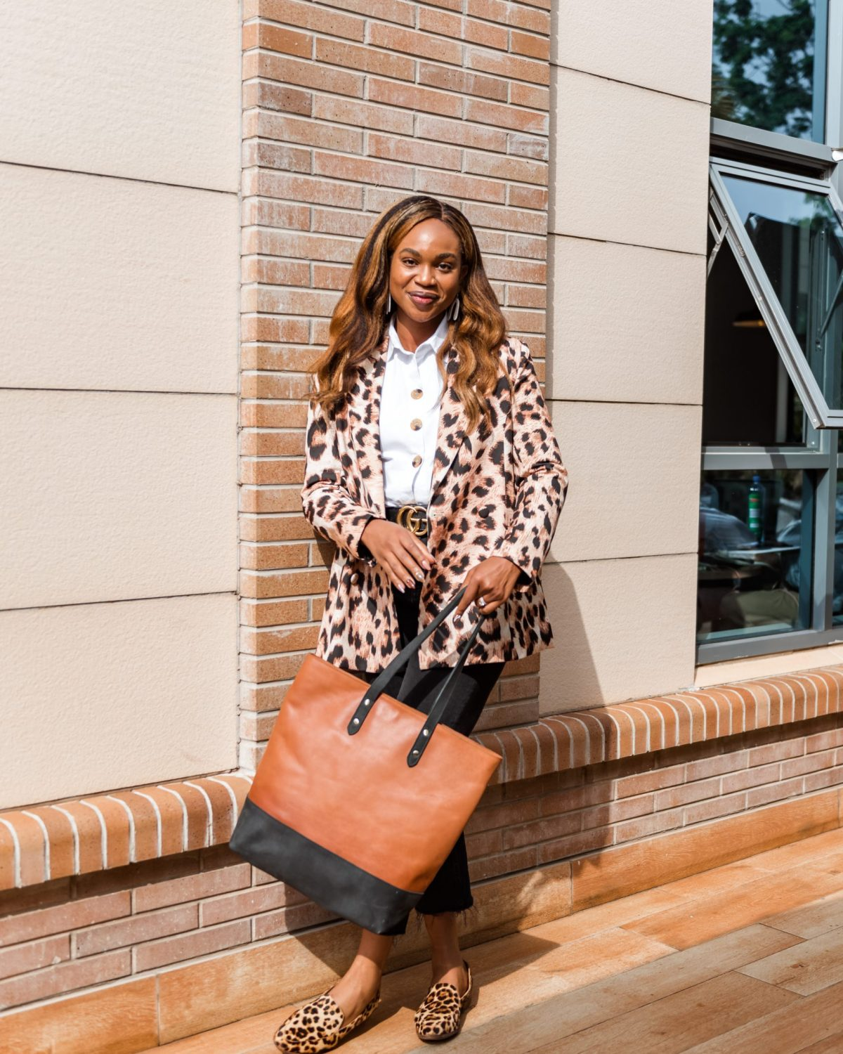 Ijeoma Kola posing outdoors with animal print blazer, white shirt, black pants and brown tote bag - How Black Owned Business Can Optimize Black History Month